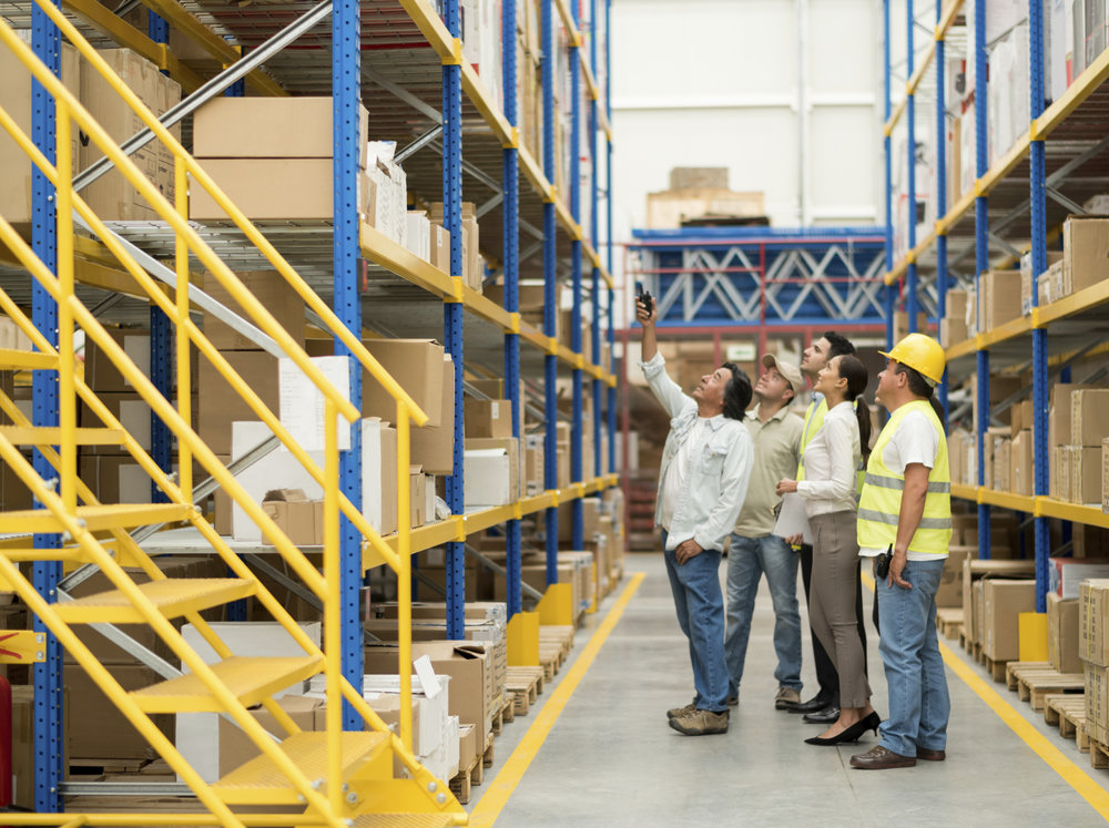 Group of people working at a warehouse and pointing at some boxes - freight transportation