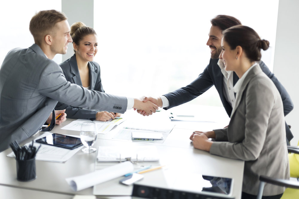 Happy couple meeting their financial advisor, shaking hands