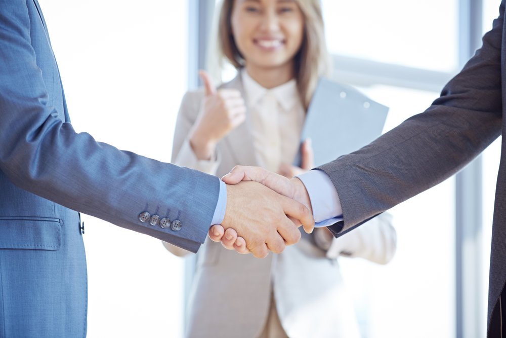 Two businessmen shaking hands, happy businesswoman giving thumbs up in the background