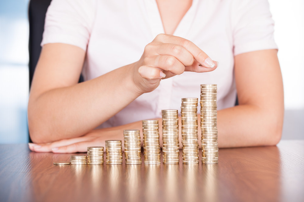 Close-up Of Businesswoman Stacking Gold Coins On Increasing Coins