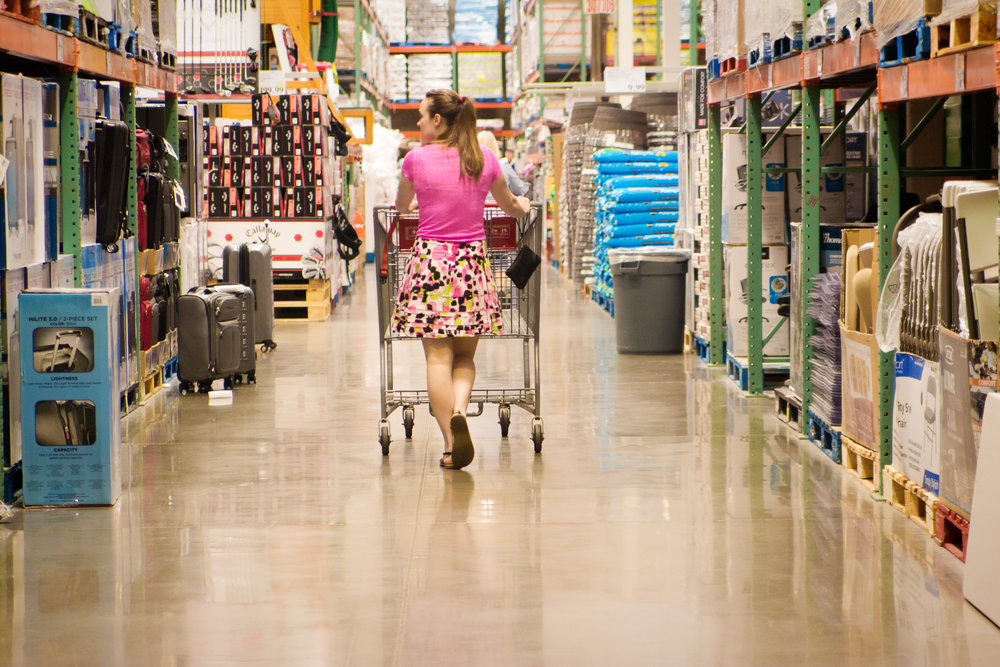 Young woman shopping in big box warehouse store for household items.