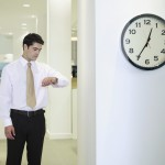 Businessman checking watch in office by clock