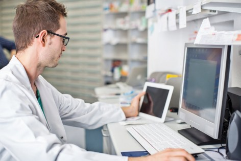 Shot of male pharmacist sitting at his desk and working with digital tablet and computer