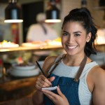 Happy waitress working at a coffee shop and looking at the camera holding a notepad