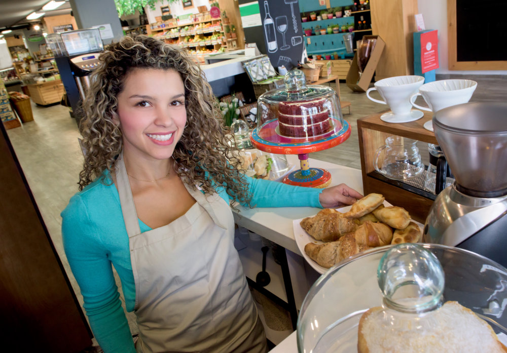 Latin American woman working at a cafe selling coffee and pastries and looking at the camera smiling