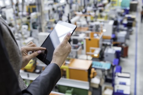 Horizontal color image of businesswoman - unrecognizable person - working with digital tablet in large futuristic factory. Woman standing on top of a balcony, holding touchpad and checking inventory of a manufacturing company on touchscreen tablet. Focus on businesswoman's hands holding black tablet, futuristic machines in background.