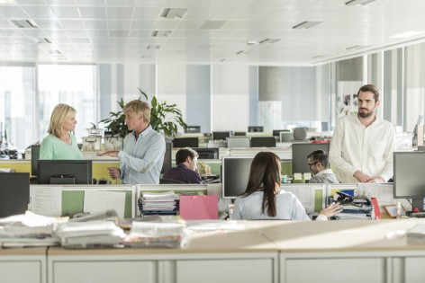 Male and female businesspeople at work with filing cabinets and paperwork in foreground. Businessmen and businesswomen interacting in modern workplace.