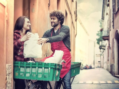 Young man on bike with apron delivering groceries to a lady