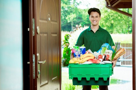 Delivery man standing at the door of the house and carrying box with groceries, smiling at camera.