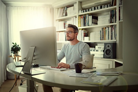 Cropped shot of a man sitting behind his computer in his home office