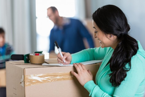 Mid adult Hispanic mother writes a to-do list as she and her family pack up to move to new home. Her husband and son are packing or moving boxes in the background.